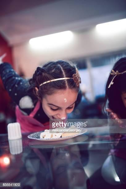 Little Girl Licking et brisant son visage dans le gâteau d'anniversaire