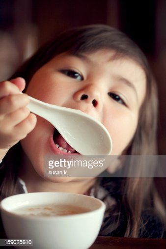 Little girl licking her spoon at breakfast. : Stock Photo