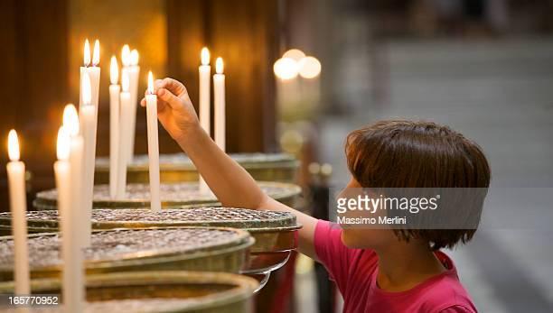 Kleines Mädchen Beleuchtung eine Kerze in der Kirche