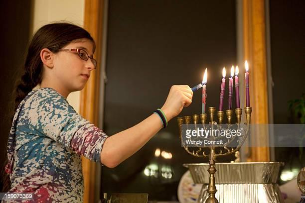 Little girl lighting Hanukkah candles
