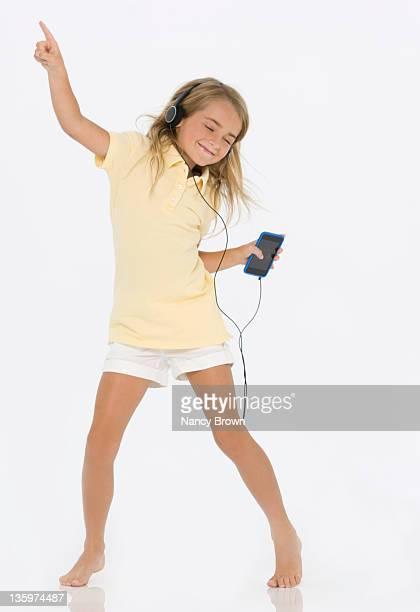 Little girl listening to music on smart phone.