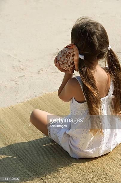 little girl listening to seashell