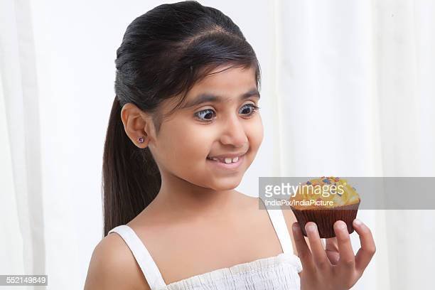 Little girl looking at a cupcake