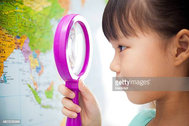 Little Girl Looking at a World Map with Magnifying Glass