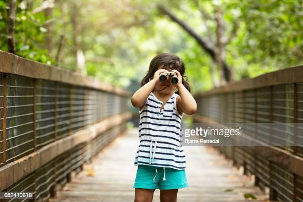 Little Girl Looking at camera through binoculars in The Daintree National Park