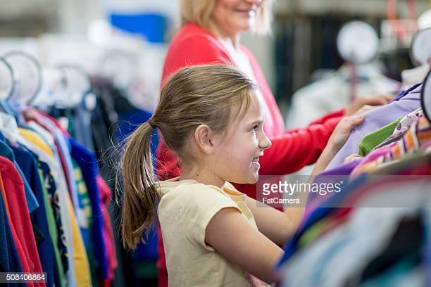 Niña pequeña observando a en la tienda de ropa