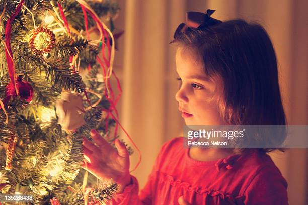 Little girl looking at lit Christmas tree