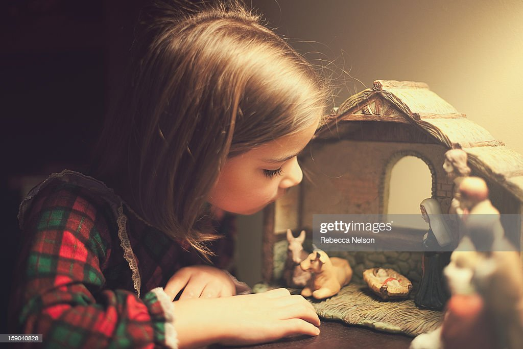Little girl looking at nativity scene