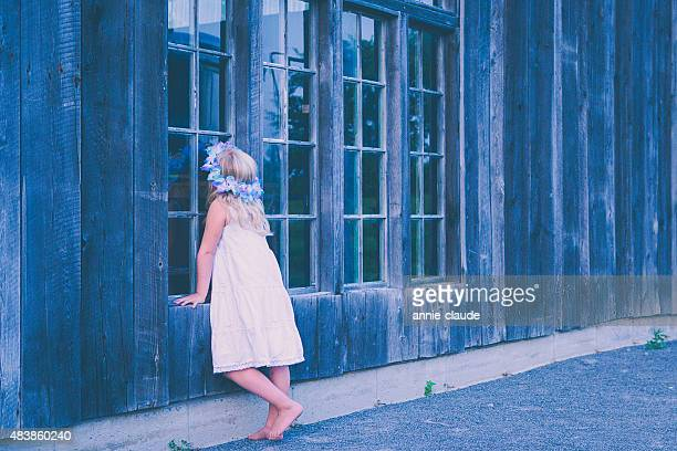 Kleines Mädchen auf der Suche in einem alten Kabine
