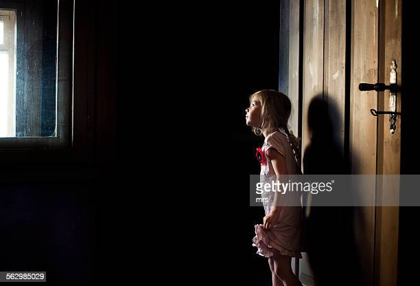 Little girl looking out window from dark room