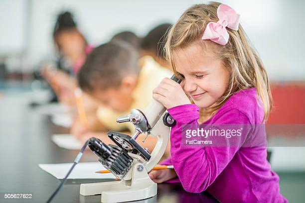 Little Girl Looking Through a Microscope