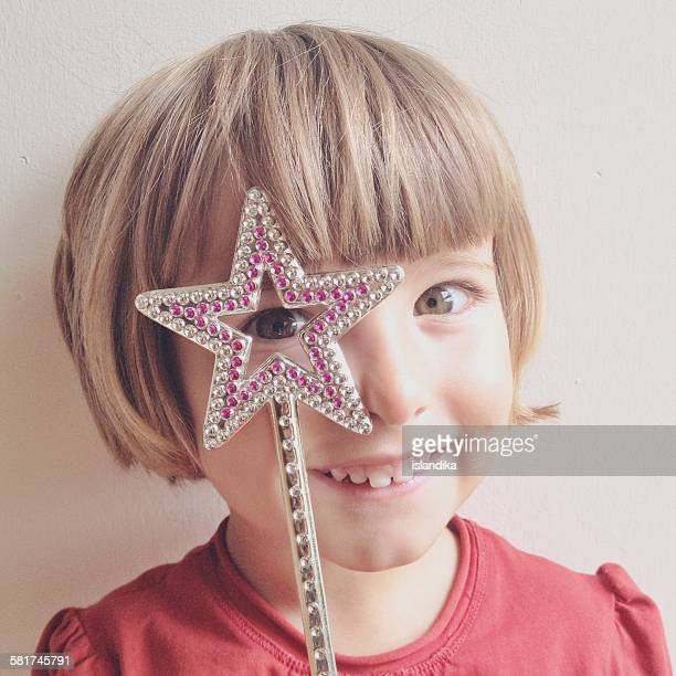 Little girl looking through star wand