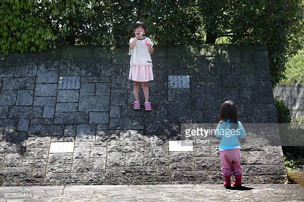 A little girl looks on as another girl blows bubbles at an evacuation centre following an earthquake on April 20 2016 in Mashiki near Kumamoto Japan...