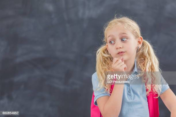 Little girl looks to the side in classroom
