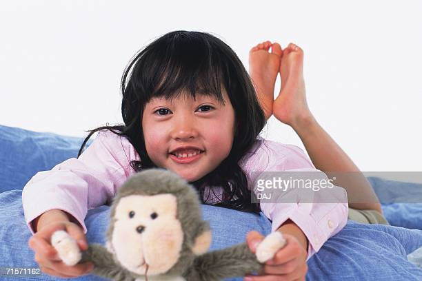 Little Girl lying on a quilt and holding a monkey doll, looking at camera, Smiling, Front View, Differential Focus
