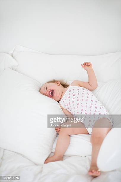 Little girl lying on bed and laughing