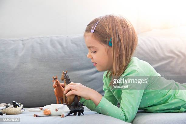 Little girl lying on couch playing with animal figurines