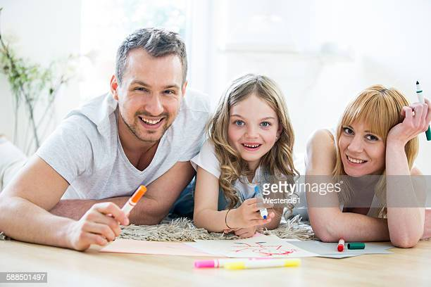 Little girl lying on floor with parents, drawing with felt tip pens