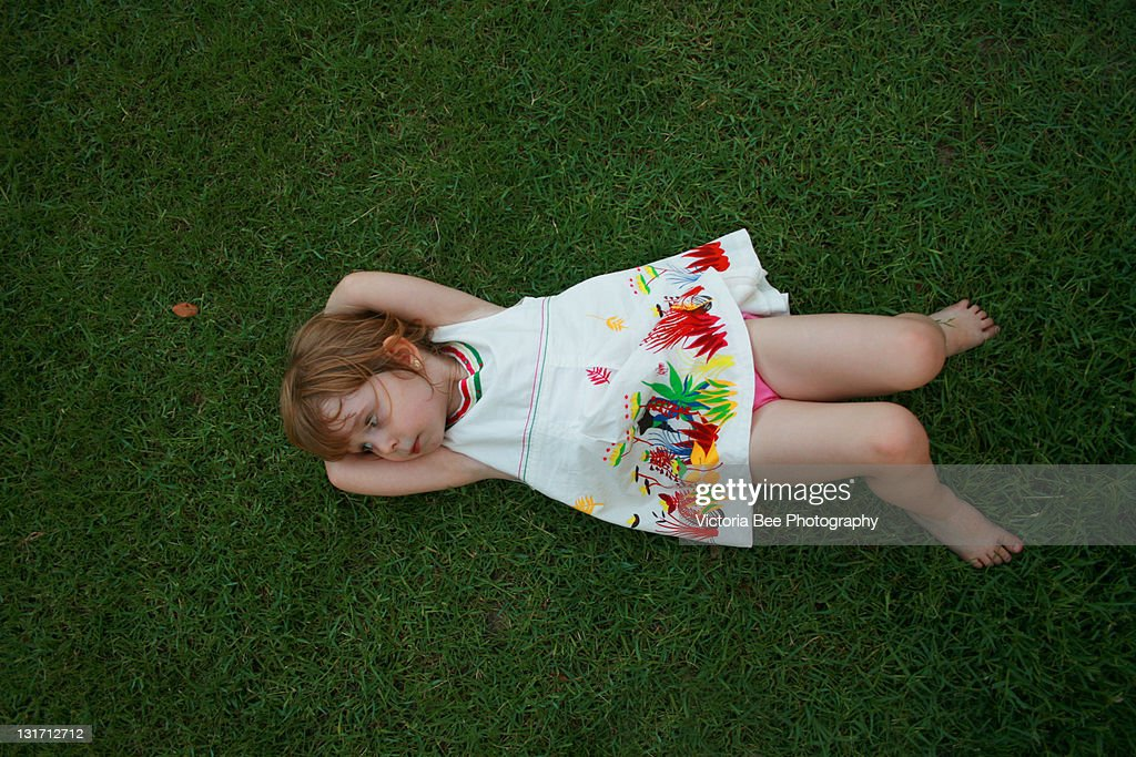 Little Girl Lying On Grass Stock Photo | Getty Images