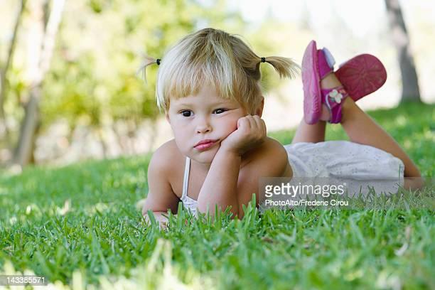 Little girl lying on grass, portrait