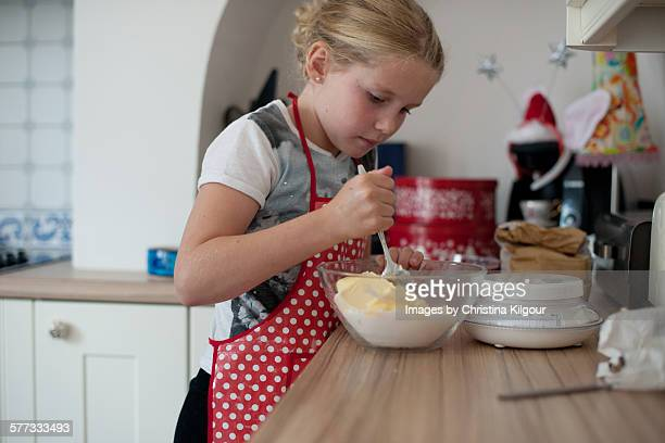 Little girl making a cake
