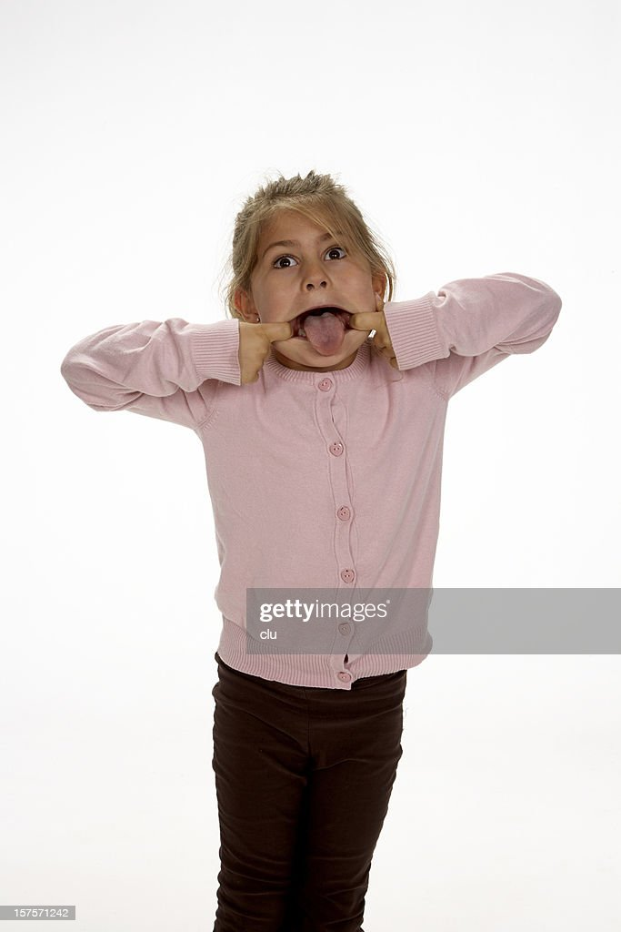 Little girl making a face sticking out the tongue : Stock Photo