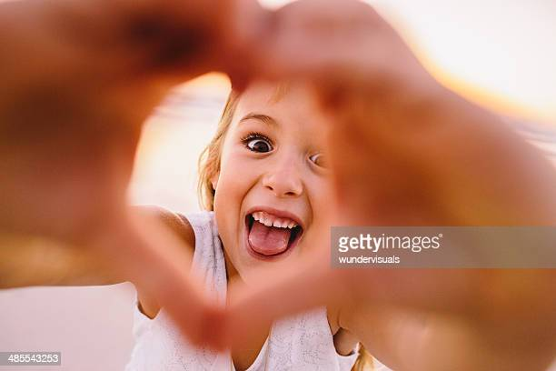Little Girl making a heart at the beach