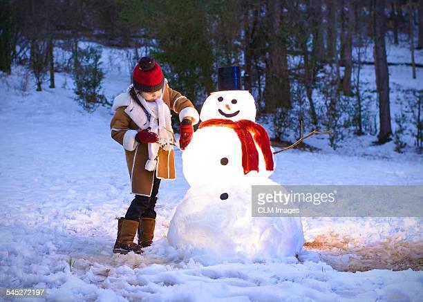 A little girl making a snowman.