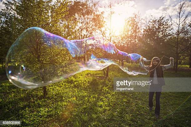 Little girl making big bubbles on spring evening