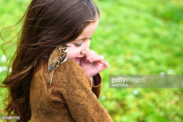 Little girl making friend with a bird