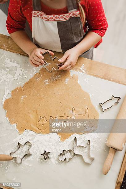 Little girl making gingerbread cookies for christmas