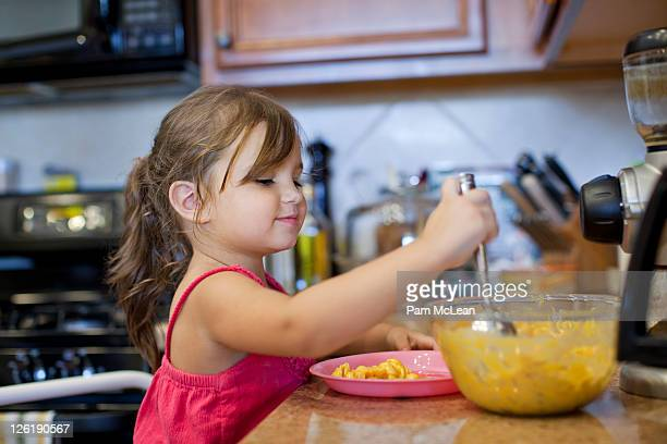 Little girl making macaroni and cheese in kitchen