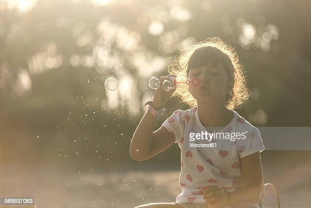 Little girl making soap bubbles in the park at twilight