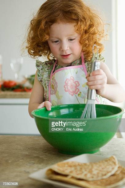 Little girl mixing ingredients in a bowl with a whisk