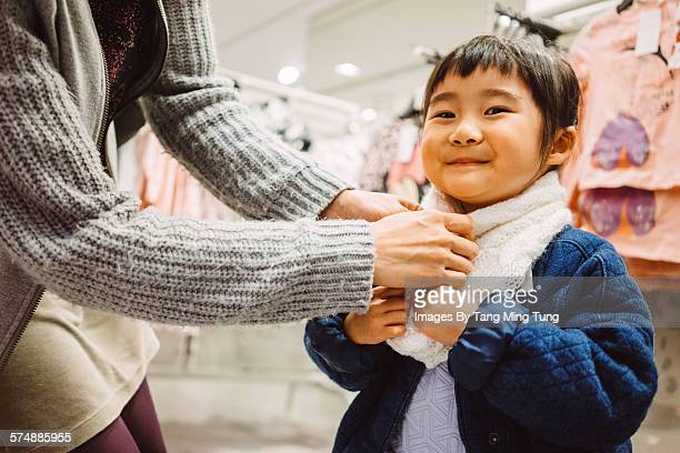 Little girl & mom trying on scarf in clothes store