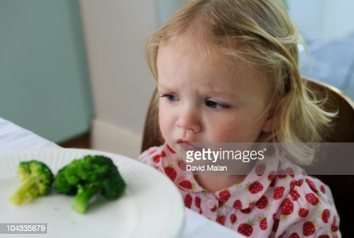 Little girl not wanting to eat broccoli