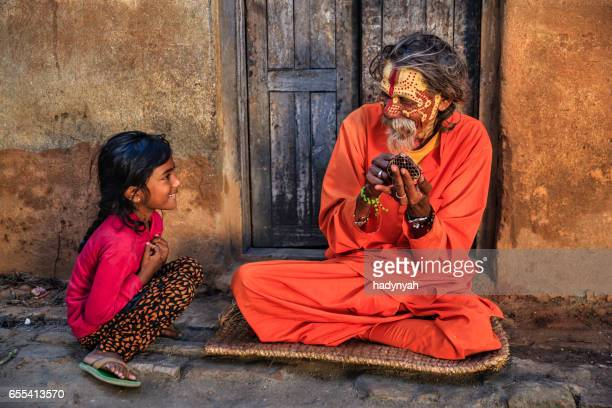 Little girl observing how Sadhu doing doing his makeup