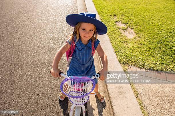 Little girl off to school in uniform on her bike