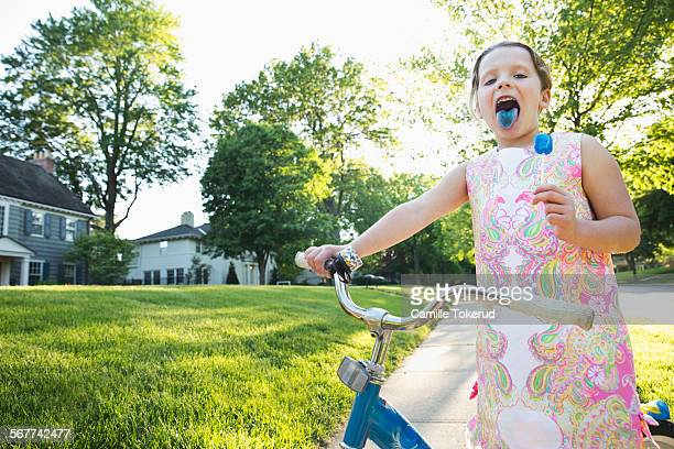 Little girl on a bicycle holding a lollypop