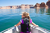 A young girl looking out on the front of a boat at beautiful Lake Powell National Recreation Area