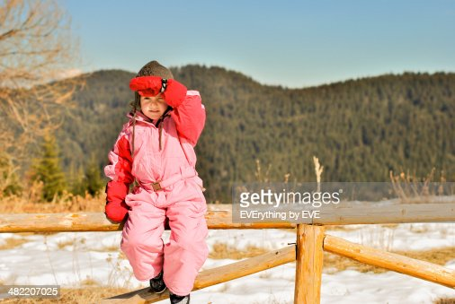 little girl on a mountain with ski equipment