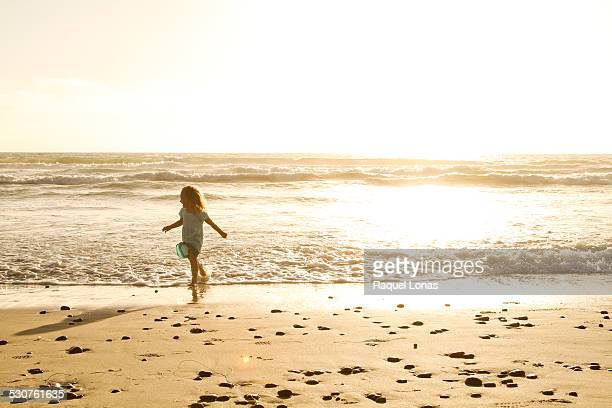 Little girl on beach running from the waves