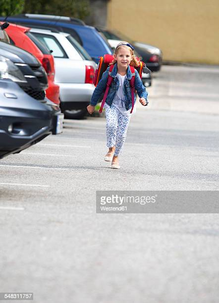 Little girl on her school way crossing parking area
