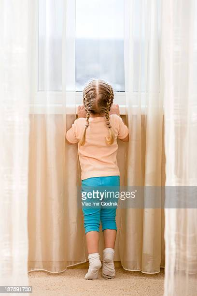 Little girl on her tiptoes trying to see out window