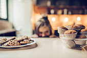 Charming little girl on kitchen is looking from under the table on sweets. Ready to eat some cookies and cakes.