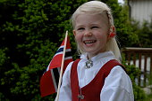Laughing little girl with flag on Norwegain constitution day. Dressed in national costume.