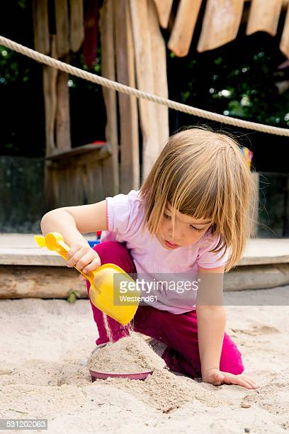 Little girl on playground balancing in sandbox