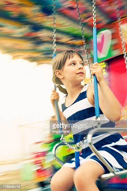 Little girl on swing carousel.