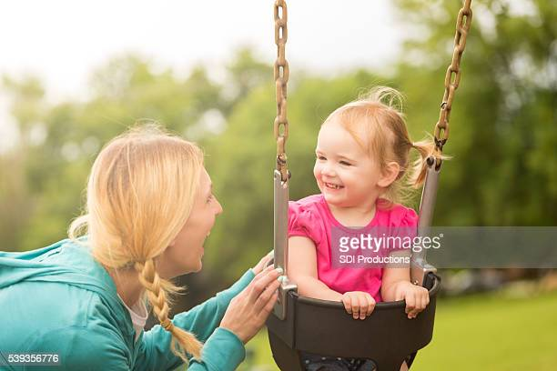 Little girl on swing smiling at her mom