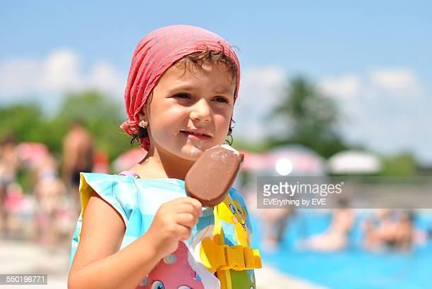 little girl on the beach eating ice cream